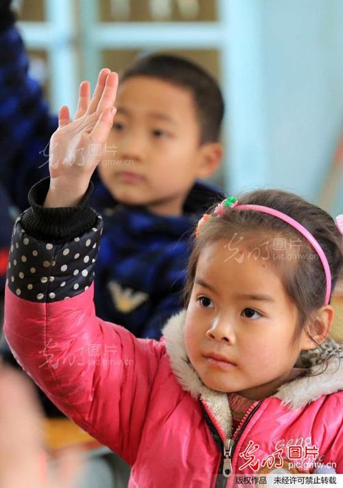 中心小学的一名小学生在课堂上举手回答老师提问.谭凯兴摄/光明图
