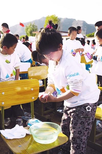 一名小学生在全球洗手日主题活动上学习正确的洗手