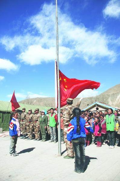 图为玉树县二完小学生与援建官兵一起升国旗,唱国歌.