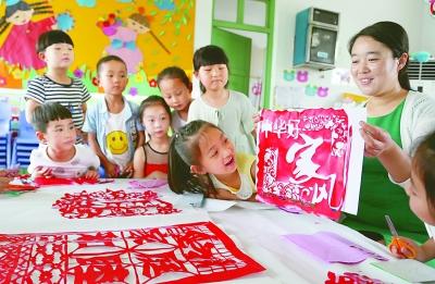 河南宝丰县汇佳幼儿园的小朋友和老师一起创作剪纸作品《中华好家风